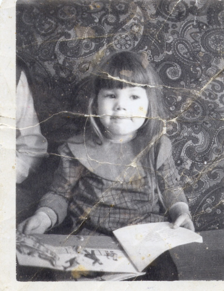 Dinah, age 4, with a book in her lap