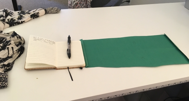 A pair of soft, loose lounge pants lies beside an open notebook with a pen laid by from making notes. Next to it is a piece of green craft paper with the edges folded over like a seam allowance.
