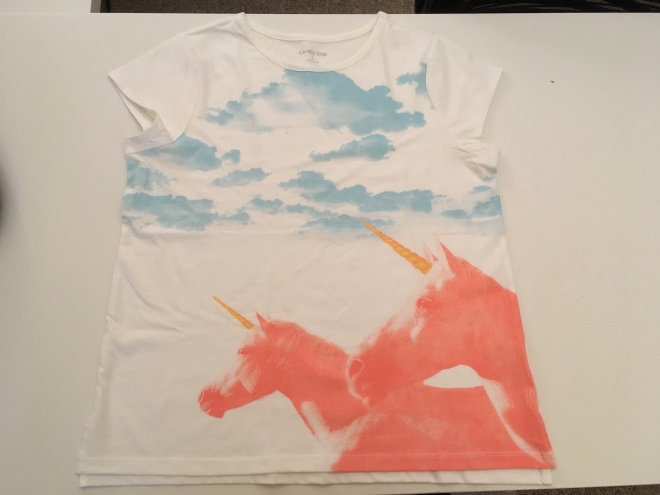 White t-shirt with a pair of pink unicorns with gold horns under fluffy blue clouds.