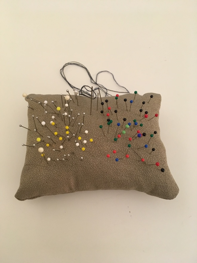 A tiny pillow-like pincushion with a variety of pins and needles sticking out of it.