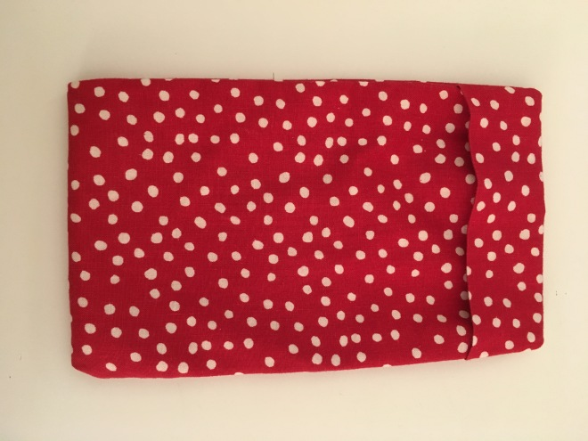 A simple rectangular bag with one end folding over to form a closure. It is made of red cotton fabric with small, irregular, white dots and has a friendly, casual feel.