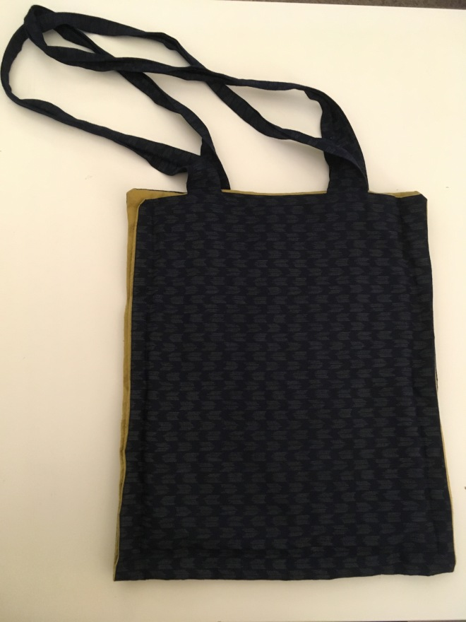 A fairly flat blue bag with soft straps and bits of green peeking out at the sides of the bag.