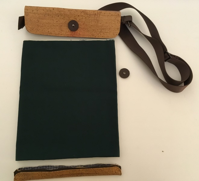 A project in progress: The bag portion is partially stitched together and sits on a table with the cork top (with straps) and footer above and below it, and a button for looping a fastener beside it, waiting to be sewn on.