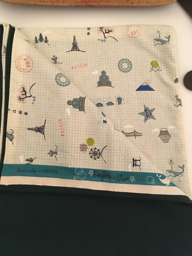 The material is folded back to reveal the whimsical fabric inside with little drawings of Mt. Fuji, a whale, a torii gate, passport stamps, etc. on a gridded background like white graph paper.