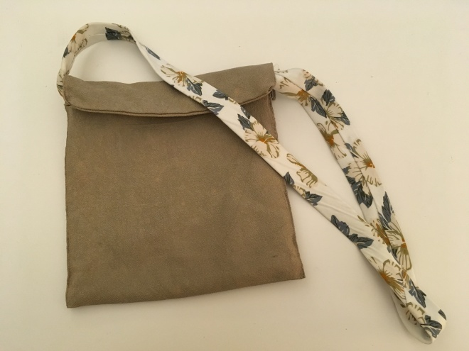 A flat, green fabric bag with a handle made from a flowery Hawaiian print necktie.