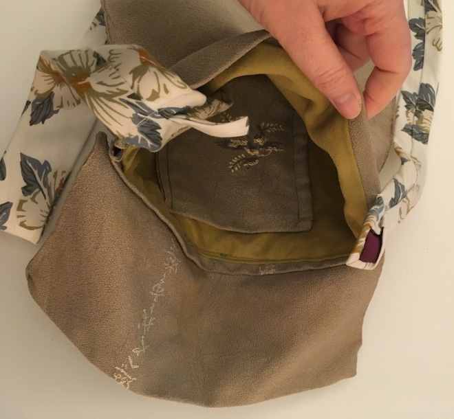 Dinah's hand holding open the bag to show the interior pocket and soft lining, and where the tie ends are stitched in to secure them as the bag straps.