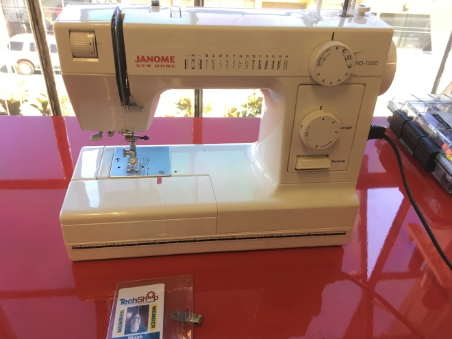 Janome New Home sewing machine on a bright red table next to Dinah's TechShop badge.
