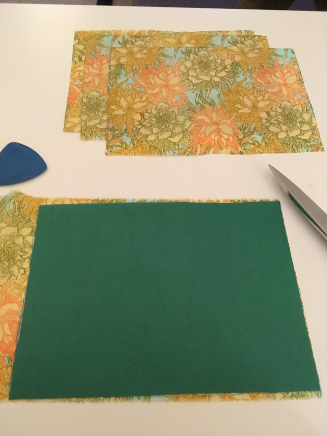Rectangles of bright flowered fabric sit on a white table. Blue tailor's chalk  has been set down after marking around a green paper pattern sitting atop uncut fabric. The point of a pair of tailor's shears sticks into the picture from the right.