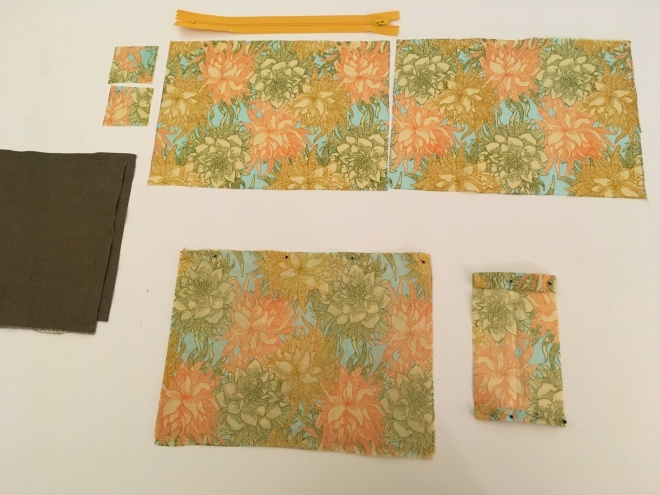 Rectangles of bright flowered fabric (in a pattern of gold, green, and coral colored dahlia flowers on a sky blue background) are neatly arranged with three smaller pieces beside them. A cheerful hot-dog-mustard-yellow zipper rests above the flowered fabric and the edge of  dark brown linen fabric rectangles is visible at the left of the picture.