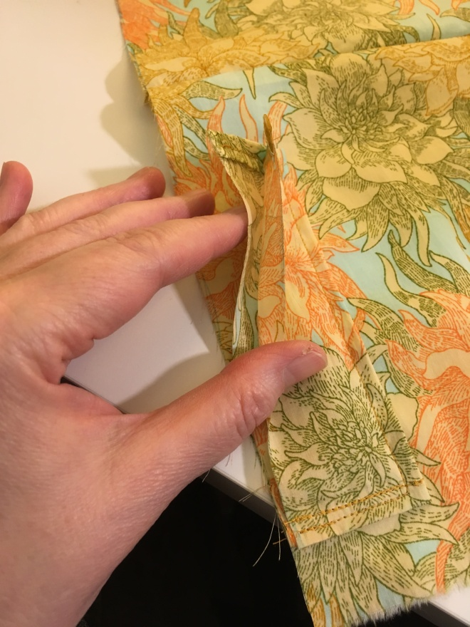 Dinah's fingers hold up the two folded sides of the pen pocket piece, now stitched to the divider layer, to show how they form a double pocket (the divider piece acting as a backing).