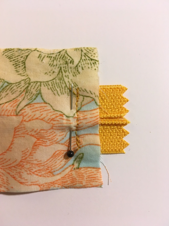Yellow zipper tape ends protrude from under a pinned piece of bright flowered fabric which has just been stitched on.