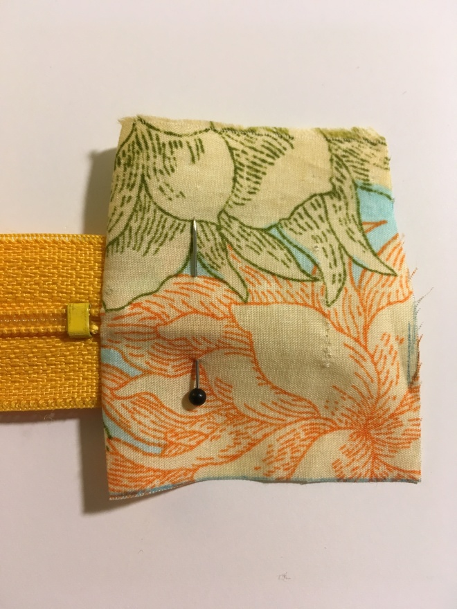 The bright flowered fabric has now been folded over to show its right side, revealing the bottom stop of the zipper, and pinned so it can be stitched into that position.
