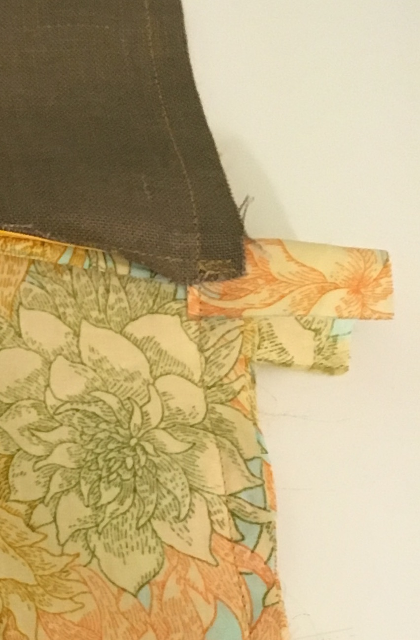 The zipper end cover sticks out to the side of the lining piece. It is folded down in this step so that its near end is stitched to the lining edges. The far edge, sticking out, will fold down into the bag when the outside is turned right side out around the lining portions.