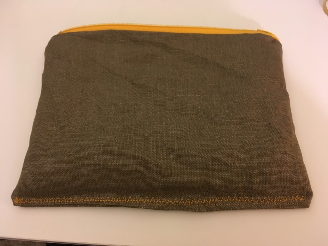 A simple brown linen rectangle with a stripe of bright yellow-gold zipper at the top and coordinating stitching across the bottom edge in a pattern of arrowheads pointing up.  One part of the bottom edge sticks down a little below the decorative stitching.