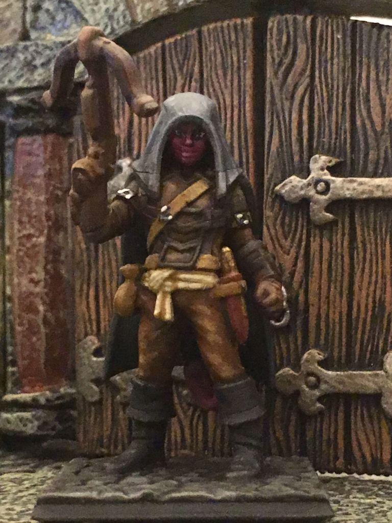 A purple/lilac skinned hooded figure wearing leather armor stands in front of a heavy wooden door, holding a crossbow in her hand and pointing it upward. She has leather armor, big cuffed boots, and a dagger at her hip. The figure and the door are both 1:60 scale miniatures.